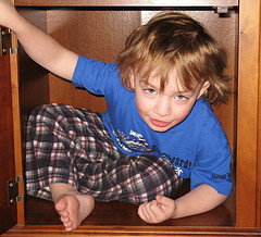 Child hiding in cupboard